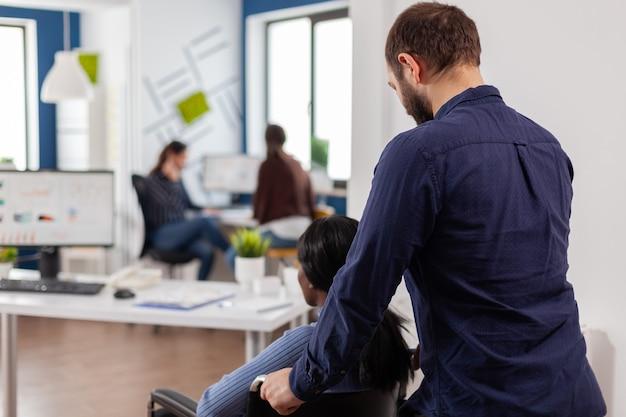 Biznesmen pomagający swojemu niepełnosprawnemu czarnemu koledze w wejściu do biura firmy