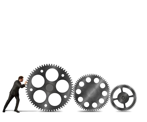 Biznesmen popycha system mechanizmu przekładni