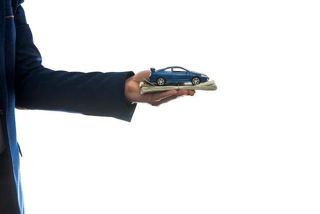 Biznesmen posiada autko i nam pieniądze na sprzedaż lub wynajem samochodu na białym tle