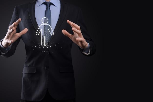 Biznesmen posiada ikonę osoby człowieka na ciemnym tle. hr ludzki, ludzie icontechnology process system business z rekrutacją, zatrudnianiem, budowaniem zespołu. koncepcja struktury organizacyjnej.