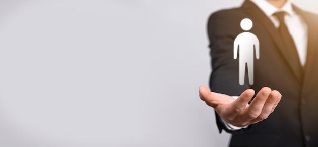 Biznesmen posiada ikonę osoby człowieka na szarym tle. hr ludzki, ludzie icontechnology process system business z rekrutacją, zatrudnianiem, budowaniem zespołu. koncepcja struktury organizacyjnej.