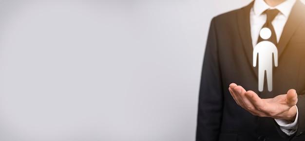 Biznesmen posiada ikonę osoby człowieka na szarym tle. hr ludzki, ludzie icontechnology process system business z rekrutacją, zatrudnianiem, budowaniem zespołu. koncepcja struktury organizacyjnej