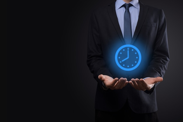 Biznesmen posiada ikonę zegara godzin ze strzałką