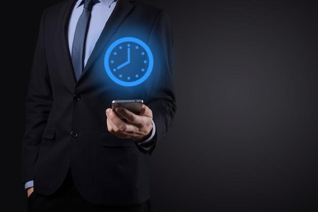 Biznesmen posiada ikonę zegara na smartfonie