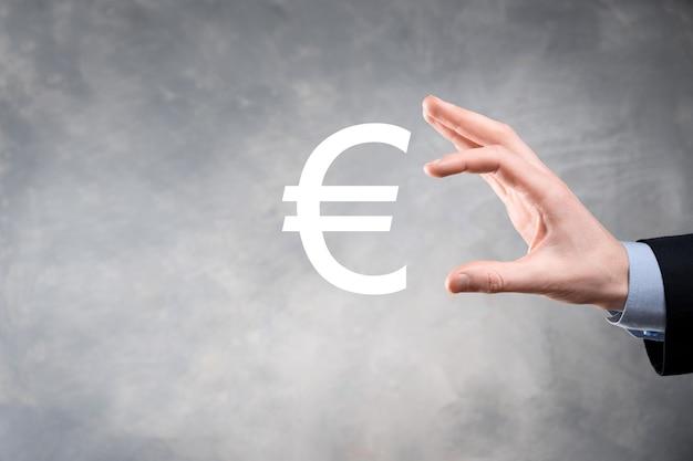 Biznesmen posiada ikony monet (eur lub euro) na ścianie ciemnego tonu. rosnące pojęcie pieniędzy na inwestycje biznesowe i finanse.
