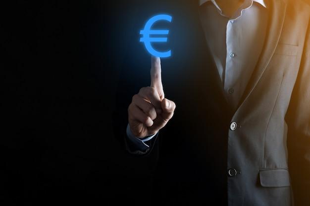 Biznesmen posiada ikony monet euro lub euro na ciemnej ścianie tonu. rosnące pojęcie pieniędzy na inwestycje biznesowe i finanse.