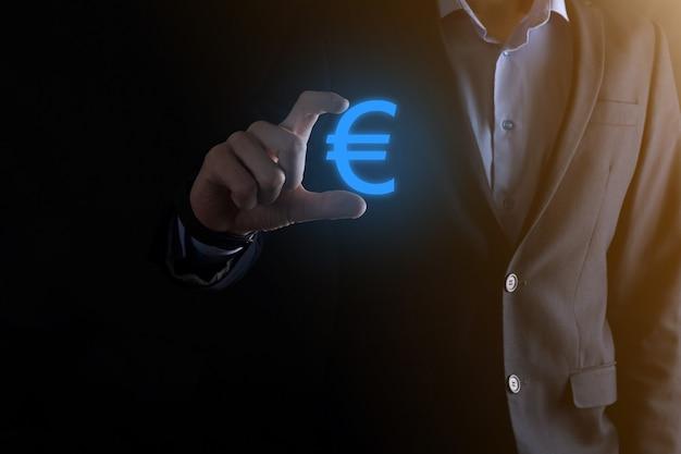 Biznesmen posiada ikony monet euro lub euro na ciemnym tle tonu
