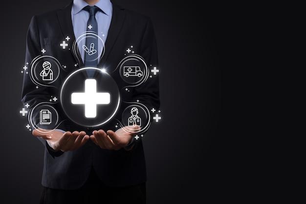 Biznesmen posiada ikony połączenia sieci wirtualnej oraz medycznej. pandemia covid-19 rozwija świadomość ludzi i zwraca uwagę na ich opiekę zdrowotną. lekarz, dokument, medycyna, karetka pogotowia, ikona pacjenta.