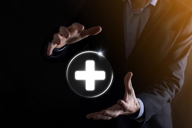 Biznesmen posiada ikony połączenia sieci wirtualnej oraz medycznej. pandemia covid-19 rozwija świadomość ludzi i zwraca uwagę na ich opiekę zdrowotną.