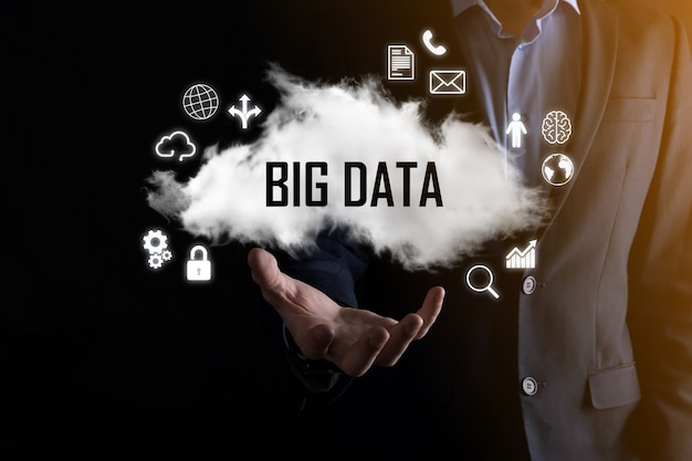 Biznesmen posiada napis big data. kłódka, mózg, człowiek, planeta, wykres, lupa, koła zębate, chmura, siatka, dokument, list, ikona telefonu.