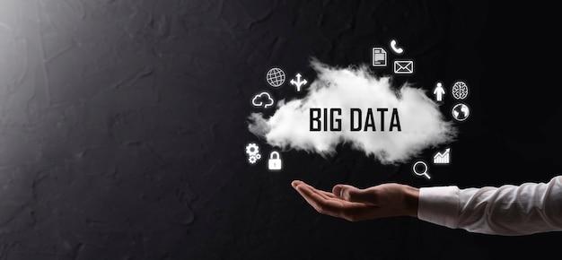 Biznesmen posiada napis, słowo big data. kłódka, mózg, człowiek, planeta, wykres, lupa, koła zębate, chmura, siatka, dokument, list, ikona telefonu.