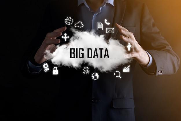 Biznesmen posiada napisowe słowo big data. kłódka, mózg, człowiek, planeta, wykres, lupa, koła zębate, chmura, siatka, dokument, list, ikona telefonu.