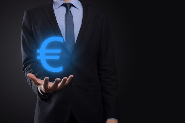 Biznesmen posiada pieniądze monety ikony eur lub euro na ciemnym tle... rosnące pojęcie pieniędzy na inwestycje biznesowe i finanse.