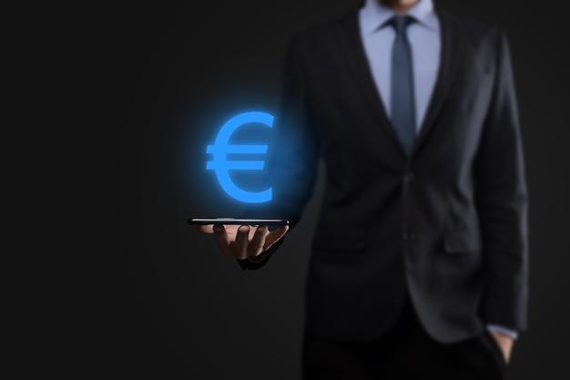 Biznesmen posiada symbole monet euro lub euro na ścianie ciemnego tonu. rosnące pojęcie pieniędzy na inwestycje biznesowe i finanse.