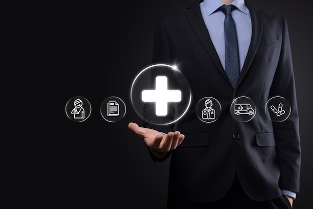 Biznesmen posiadają ikony połączenia wirtualnego oraz medycznego sieci. pandemia covid-19 rozwija świadomość ludzi i zwraca uwagę na ich opiekę zdrowotną. lekarz, dokument, medycyna, karetka pogotowia, ikona pacjenta.