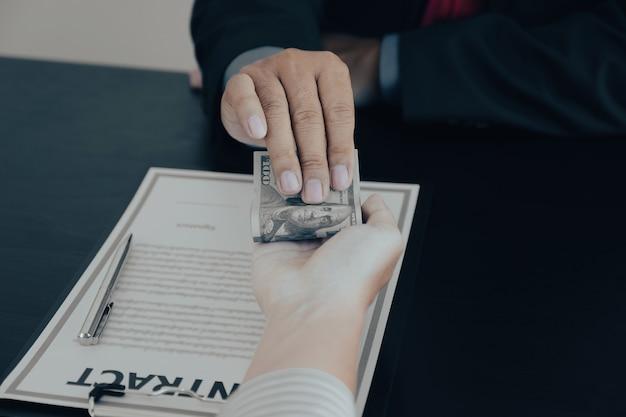 Biznesmen posiadający banknot dolarowy pieniądze, aby przekupić koncepcję antykorupcyjną urzędników finansowych
