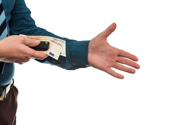 Biznesmen posiadający banknoty euro i kluczyki do samochodu na białym tle na białe tło zbliżenie