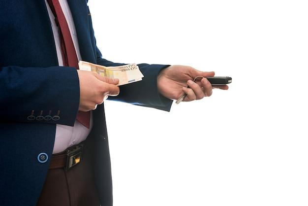 Biznesmen posiadający banknoty euro i kluczyki do samochodu na białym tle na białej ścianie zbliżenie. kup lub wynajmij koncepcję samochodu