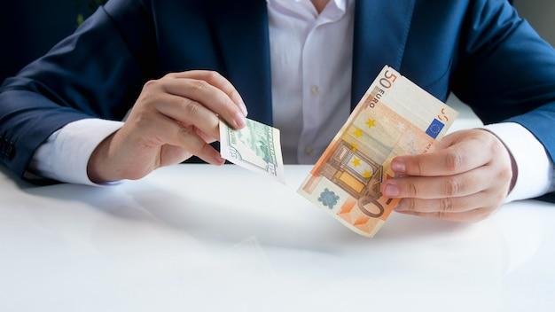 Biznesmen posiadający banknoty pieniądze euro i dolara.