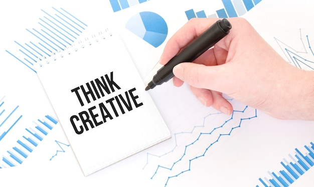 Biznesmen posiadający czarny marker, notatnik z tekstem think creative