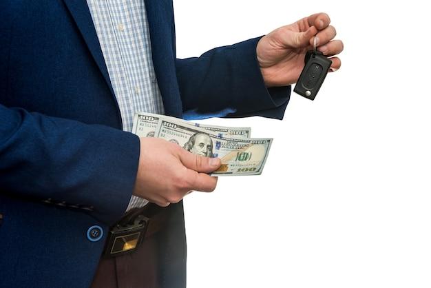 Biznesmen posiadający dolary i kluczyki do samochodu na białym tle. kup lub wynajmij koncepcję samochodu