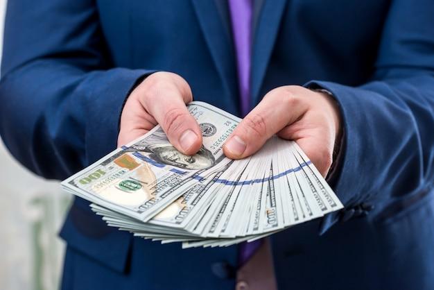 Biznesmen posiadający dużą ilość dolara i daje