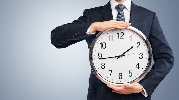 Biznesmen posiadający duży zegar w ręce, koncepcja czasu biznesowego