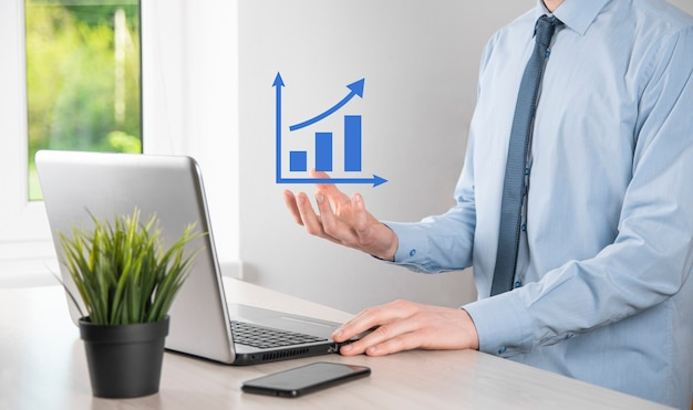 Biznesmen posiadający holograficzne wykresy i statystyki giełdowe osiągają zyski. koncepcja planowania wzrostu i strategii biznesowej. wyświetlacz dobrej jakości ekranu cyfrowego.