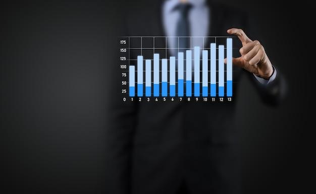 Biznesmen Posiadający Holograficzne Wykresy I Statystyki Giełdowe Osiągają Zyski. Koncepcja Planowania Wzrostu I Strategii Biznesowej. Wyświetlacz Dobrej Jakości Ekranu Cyfrowego. Premium Zdjęcia