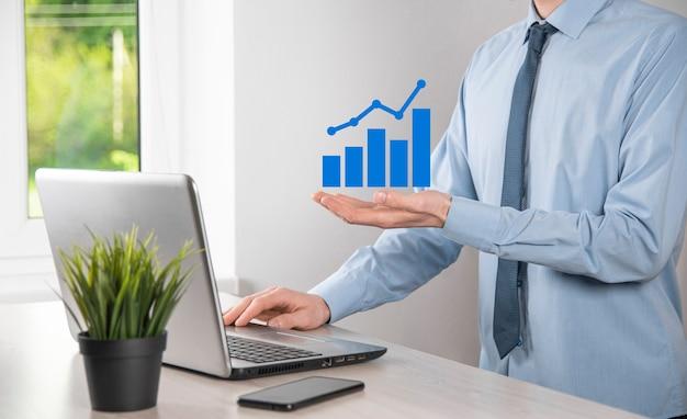 Biznesmen posiadający holograficzne wykresy i statystyki giełdowe osiągają zyski. koncepcja wzrostu