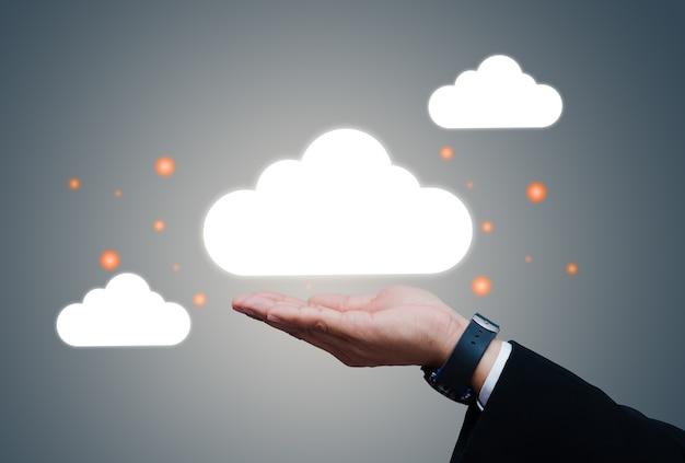 Biznesmen posiadający ikonę cloud computing sieci i informacje o połączeniu danych w ręku.