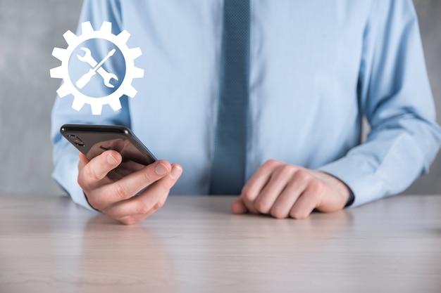 Biznesmen posiadający ikonę koła zębatego z narzędziami. gearing. concept cyfrowego diagramu ostrości docelowej, interfejsów wykresu, wirtualnego ekranu interfejsu użytkownika, sieci połączeń.