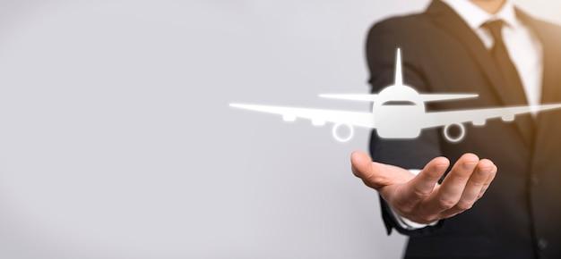 Biznesmen posiadający ikonę samolotu w jego ręce. zakup biletów online.podróże.