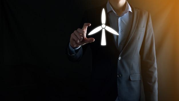 Biznesmen posiadający ikonę wiatraka, który wytwarza energię środowiska. ciemna ściana.