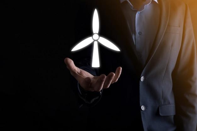 Biznesmen posiadający ikonę wiatraka, który wytwarza energię środowiska. ciemne tło.
