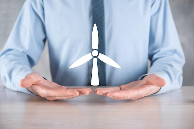 Biznesmen posiadający ikonę wiatraka, który wytwarza energię środowiska.