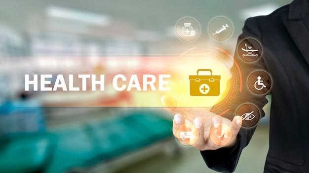 Biznesmen posiadający ikony z symbolami medycznymi na rozmytym tle