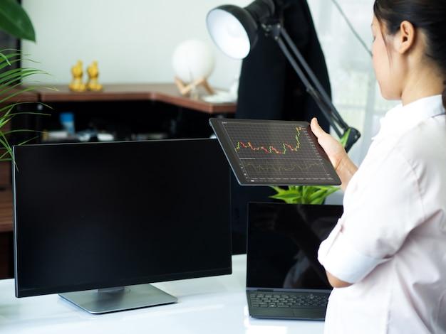 Biznesmen posiadający inteligentne urządzenie z wykresem giełdowym i handlem