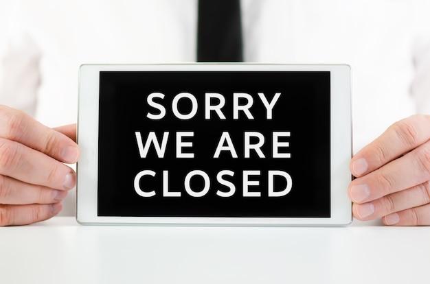 Biznesmen posiadający inteligentny tablet ze znakiem przepraszamy, że jesteśmy zamknięte
