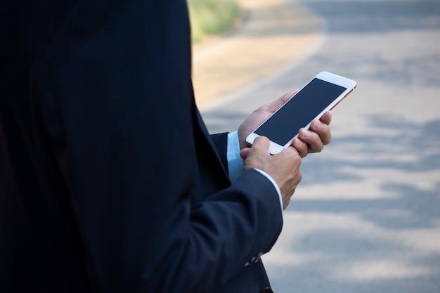 Biznesmen posiadający inteligentny telefon komórkowy i za pomocą smartfona do połączenia biznesowego