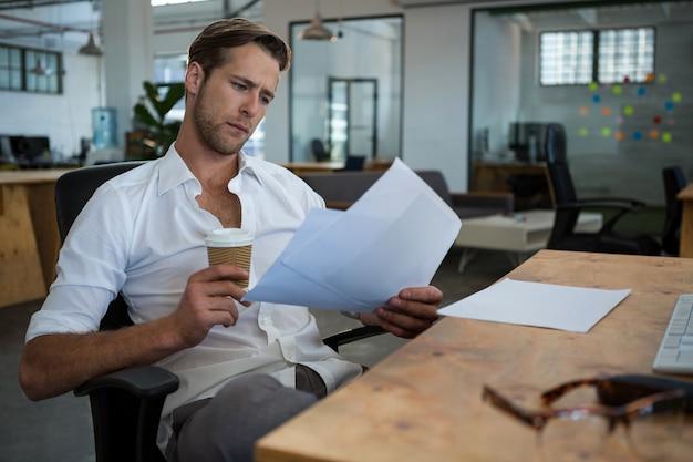Biznesmen posiadający jednorazową filiżankę kawy podczas czytania dokumentu przy biurku