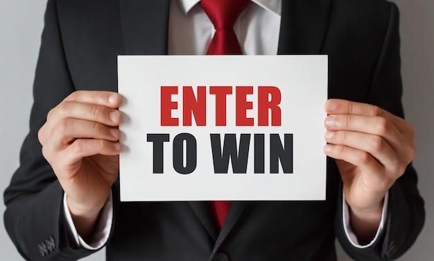 Biznesmen posiadający kartę z tekstem enter, aby wygrać