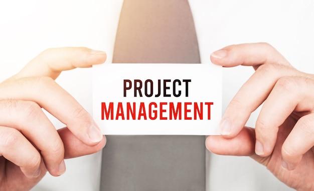 Biznesmen posiadający kartę z tekstem zarządzanie projektami, koncepcja biznesowa