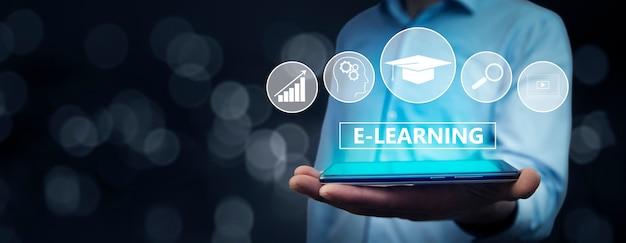 """Biznesmen posiadający komputer typu tablet z tekstem """"e-learning"""" na wirtualnym ekranie. pomysł na biznes."""