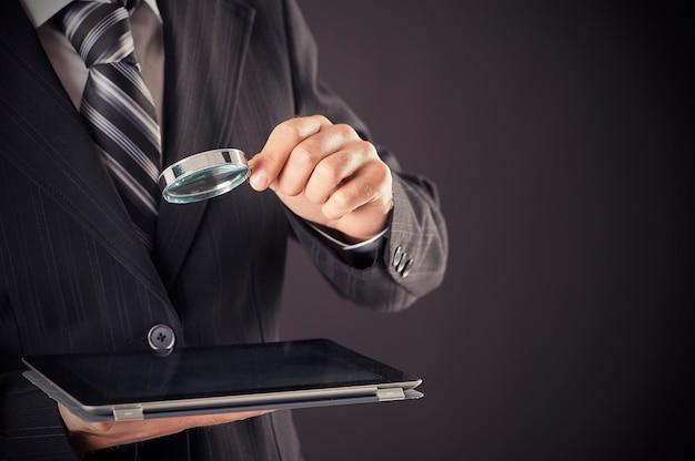 Biznesmen posiadający koncepcję szkła powiększającego i cyfrowego tabletu