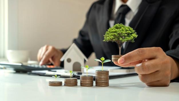 Biznesmen posiadający monetę z drzewem rosnącym na monetach i drzewem rosnącym na ułożonych monetach, koncepcja rozwoju biznesu, finanse, inwestycje