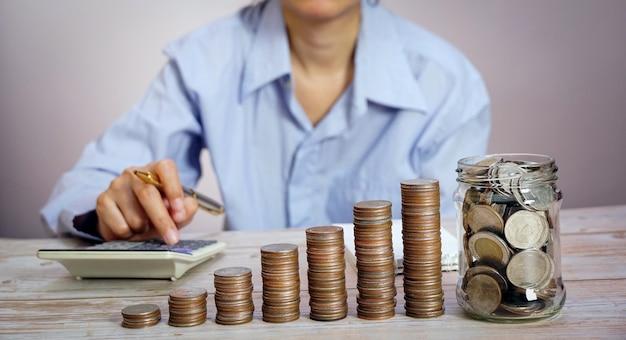 Biznesmen posiadający monety wkładające koncepcję szkła, oszczędzając pieniądze na księgowość finansową