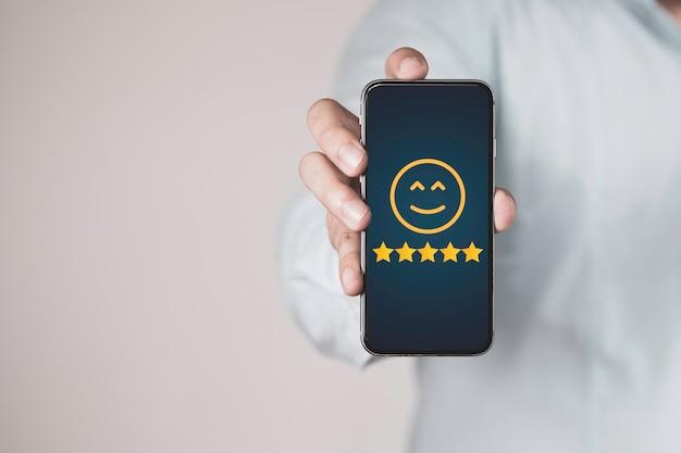 Biznesmen posiadający smartfon i pokazujący wynik oceny klienta online na pięć gwiazdek.