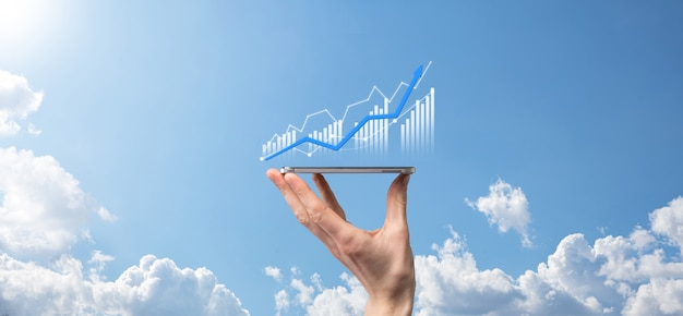 Biznesmen posiadający tablet i pokazujący holograficzne wykresy i statystyki giełdowe zyskują zyski. koncepcja planowania wzrostu i strategii biznesowej. wyświetlacz dobrej jakości ekranu cyfrowego.
