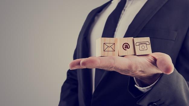 Biznesmen posiadający trzy drewniane kostki z symbolami kontaktu